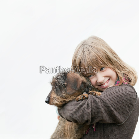 portrait of girl embracing dog in