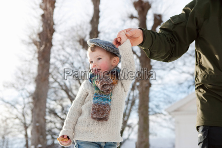 scandinavian boy guided by fathers hand