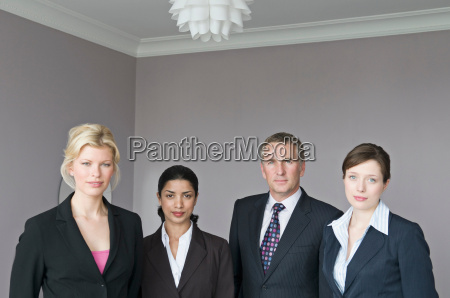 four business people looking to camera