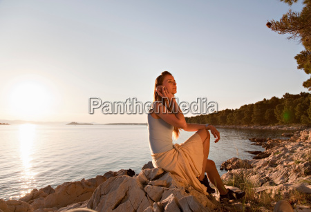 woman listening to shell at beach