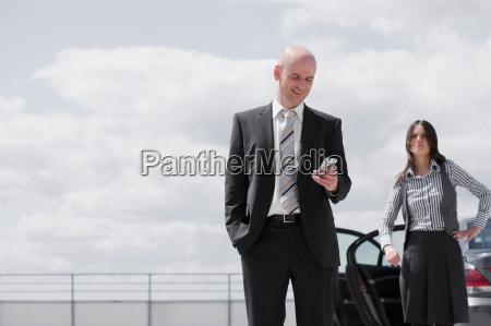 man glancing at phone woman waiting