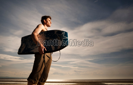 man with boogie board on beach