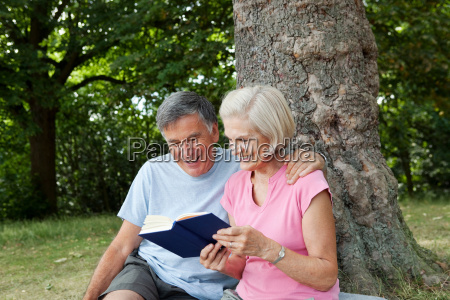 couple sharing book in park
