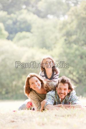 family lying on blanket in countryside