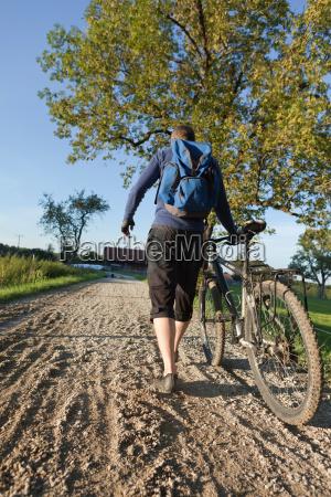 man walking with mountain bike