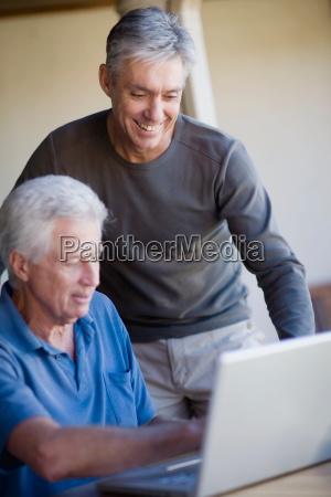 older men using laptop together