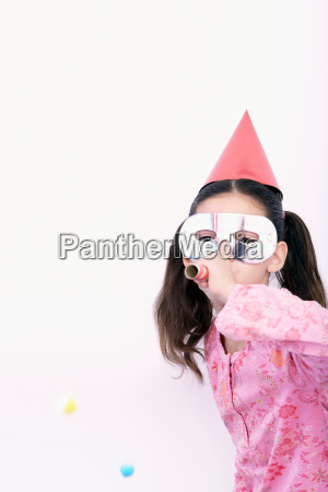 young girl blowing in a blowpipe