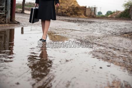business woman walking at muddy farm