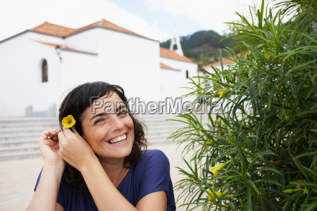 woman putting flower in her hair
