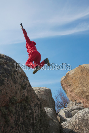 man jumping between boulders