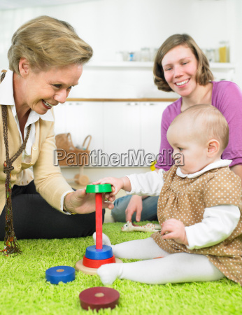 women and baby playing together