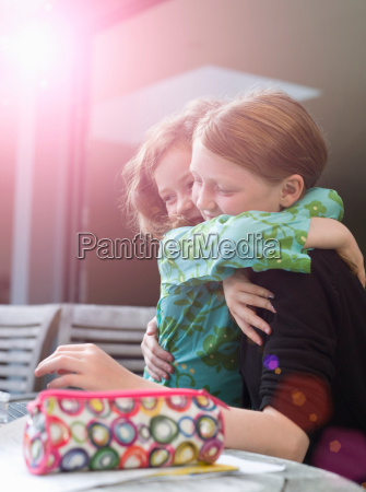 two young sisters hugging in sunlight