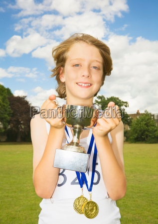 boy athlete with trophy and medals