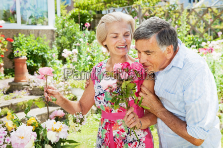 man smelling flowers in womans hand