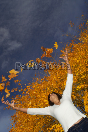 girl in autumn throwing leaves up