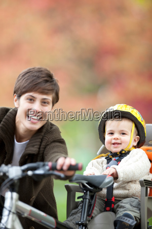 woman and child cycle together in
