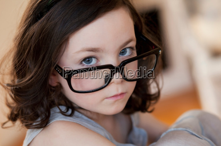 little girl wearing huge pair of