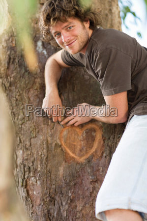 smiling man carving heart in tree