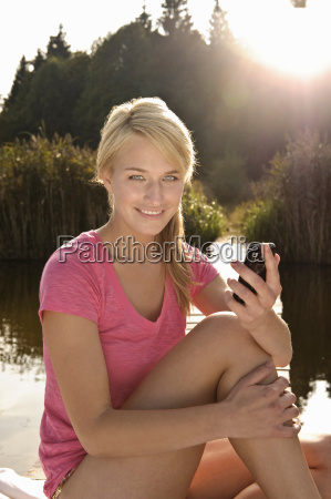 young woman using mobile phone smiling