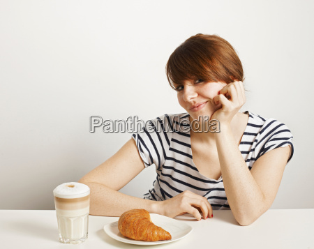 women with croissant and coffee