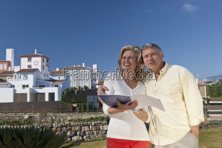 mature couple holding real estate booklet