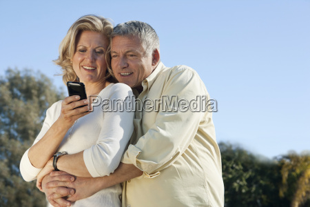 mature couple using smart phone together