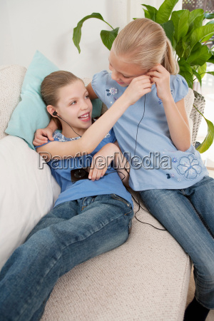 two girls listening to an mp3