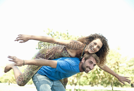 couple playing airplane in park