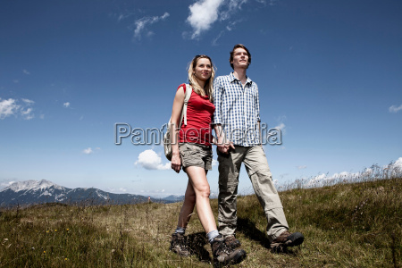 couple walking in grassy field