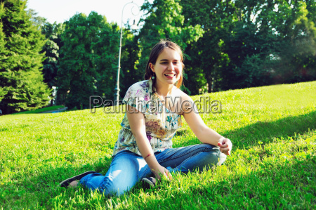 woman sitting in grass in park