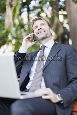 businessman working on laptop in park