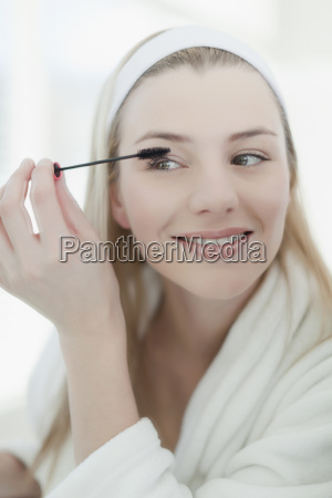 smiling woman applying makeup