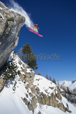 skier in midair on snowy mountain