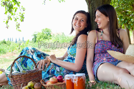 smiling women picnicking in orchard