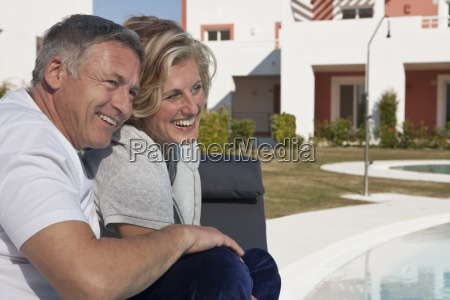 mature couple relaxing by pool