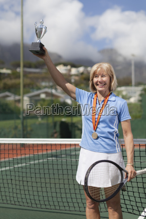 older woman with trophy on tennis