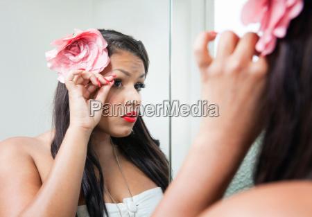 woman adjusting her makeup in mirror
