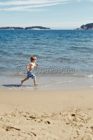 boy running in waves on beach