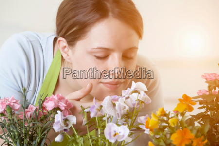 woman smelling flowers plants indoors