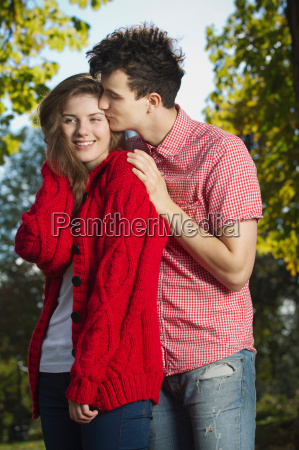 teenage couple kissing in park