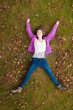teenage girl laying in grass in