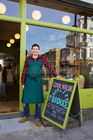 smiling grocer standing outside store