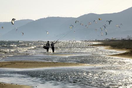 couple flying kites on beach