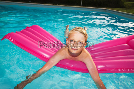 boy playing on raft in swimming