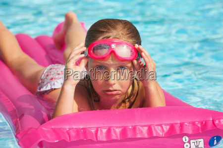 girl floating on raft in swimming