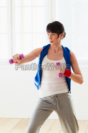 woman lifting weights indoors