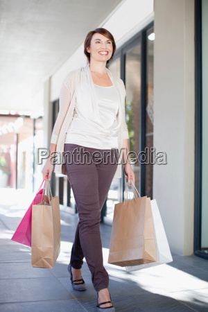 woman carrying shopping bags on street