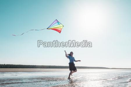 woman flying kite on beach