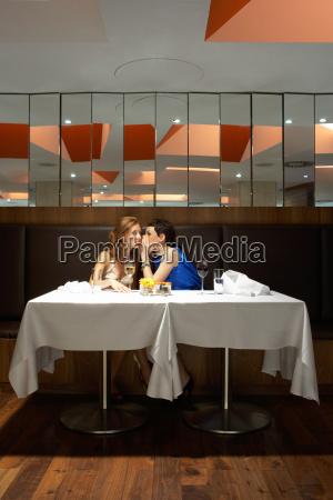 two women in a restaurant whispering