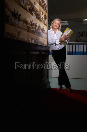 businesswoman in a hallway with binders